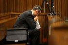 Oscar Pistorius blows his nose after reaching for a bucket as he listened to cross questioning about the events surrounding the shooting death of his girlfriend. Photo / AP