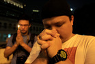 Men offer prayers during a candlelight vigil for passengers aboard a missing Malaysia Airlines plane. Photo / AP