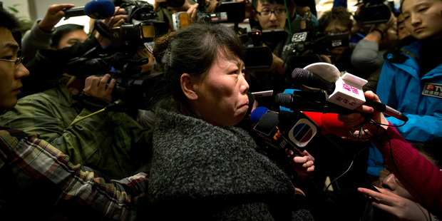A Chinese relative of passengers aboard a missing Malaysia Airlines plane is surrounded by media. Photo / AP