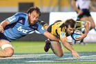 Blues Chris Lowrey tries to stop the flying Hurricanes captain Conrad Smith. Photo / Greg Bowker