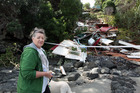 Shirley Harris with her demolished bach caused by Cyclone Wilma in Onetangi on Waiheke Island. Photo / Herald on Sunday