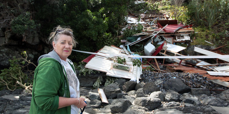Shirley Harris with her demolished bach caused by Cyclone Wilma in Onetangi on Waiheke Island. Photo / Herald on Sunday