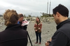 Eleanor Catton in front of the cameras on the beach at Hokitika during her fundraising visit.