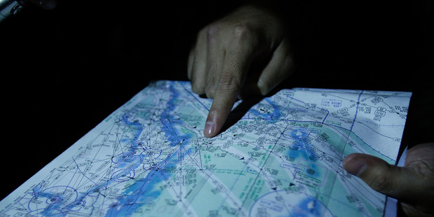 Capt. Syukri of the Malaysian Air Forces shows the flight path on a map during a search and rescue mission flight for the missing jet. Photo / Getty Images