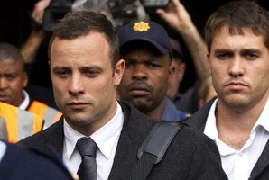 Oscar Pistorius, left, with unidentified man leaves the high court in Pretoria. Photo / AFP
