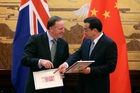Prime Minister John Key and Premier Li Keqiang exchange banknotes in Beijing. Photo / AP