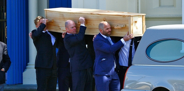 Anton Oliver (front) and other pallbearers carry Frank Oliver's coffin.