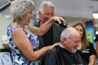 Whangarei Mayor Sheryl Mai deals to her husband's hair. Photo / APN