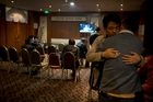 Relatives of Chinese passengers aboard the missing Malaysia Airlines MH370 comfort each other as they wait for a news briefing by the airline's officials at a hotel ballroom in Beijing yesterday. At left: New Zealand passenger Paul Weeks and his wife Danica. Photo / AP