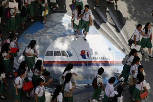 Students from the Benigno 'Ninoy' Aquino High School walk on a mural depicting the missing Malaysia Airlines plane. Photo / AP