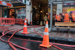 Firemen pump out water from The Strand Arcade basement. Photo / Herald on Sunday /Doug Sherring