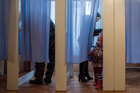 A young girl peeks out of a voting booth at a polling station during the Crimean referendum, in Orlinoe, near Sevastopol, Ukraine. Photo / AP