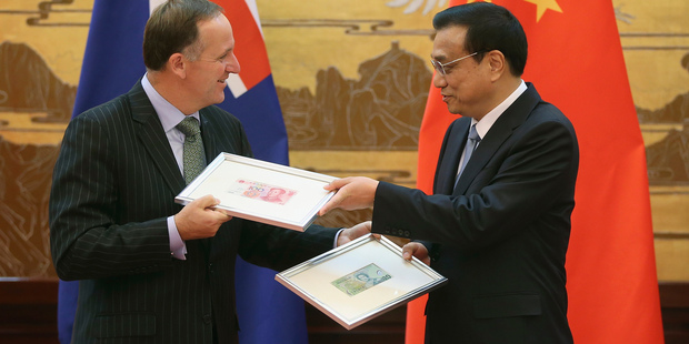 New Zealand Prime Minister John Key, left, and Chinese Premier Li Keqiang exchange Chinese Yuan and New Zealand Dollar banknotes. Photo / AP
