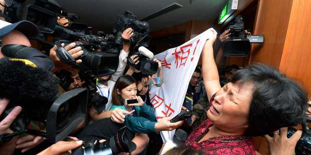 A Chinese relative of passengers aboard the missing plane cries as she holds a banner in front of journalists reading 'We are against the Malaysian government for hiding the truth'. Photo / AP