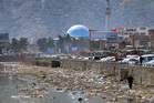 A man picks through garbage along the Kabul River in Kabul, Afghanistan. A luxury hotel in the city is reported to have come under attack by gunmen. Photo / AP