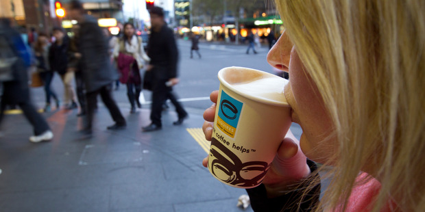 A woman drinks a regular flat white coffee from Esquires on Queen Street, Auckland. Photo / Sarah Ivey