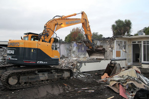 A digger demolishing an earthquake damaged house on Dallington Terrace.