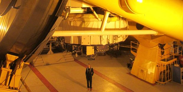 Toby Hendy looks minute standing beneath the massive CFHT telescope in Hawaii