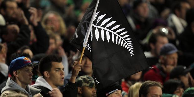 John Key backs a silver fern flag. Photo / Janna Dixon