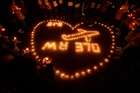 Candles flicker for Flight MH370. Photo / AP