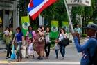 Locals in Bangkok walk past demonstrators. Photo / AP