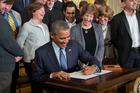 Left-handed US President Barack Obama, center, signs a Presidential Memorandum. Photo / AP