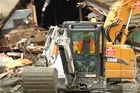 Workers have been using heavy equipment to try to clear debris. Photo / AP