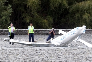 A police photographer at the scene of yesterday's plane crash which killed two men. Photo / Paul Taylor
