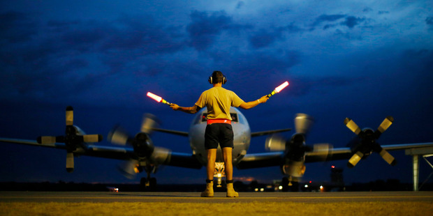 A ground controller guides a Royal Australian Air Force AP-3C Orion on the tarmac upon its return from a search for Malaysian Airlines flight MH370. Photo / Getty Images