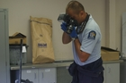 Constable Barry Murray photographing an item of interest seized in the course of this week's recovery operation.