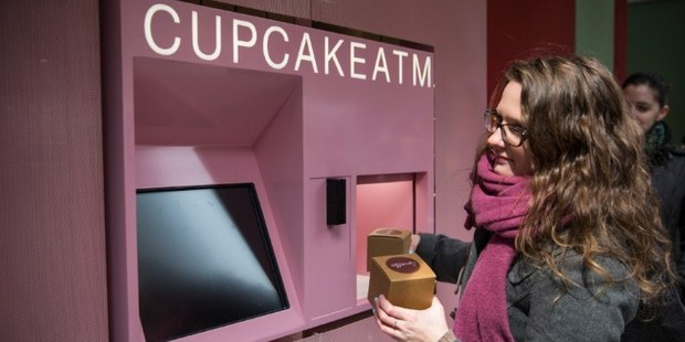 A woman takes her order of cupcakes after using a Cupcake ATM created by Sprinkles bakery in New York City. Photo / AFP