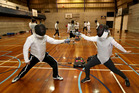 In Auckland Grammar's gym, Rachel Grunwell learns a valuable lesson from fencing coach Rob Ogg: the mind must outpace the foil or sword. Photo / Getty Images