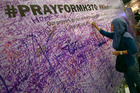 A woman leaves a message for passengers aboard a missing Malaysia Airlines plane, at a shopping mall in Petaling Jaya, near Kuala Lumpur. Photo / AP