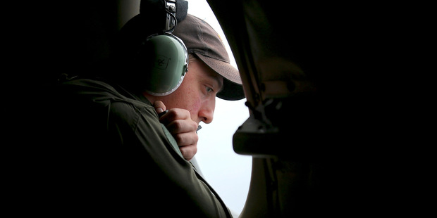A crew member on board a Royal Australian Air Force AP-3C Orion, searches for the missing Malaysia Airlines Flight 370 in the southern Indian Ocean. Photo / AP