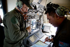 Crew members aboard a Royal Australian Air Force AP-3C Orion aircraft observe navigation maps as they search for missing Malaysian Airlines flight MH370 over the southern Indian Ocean. Photo / AP