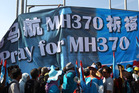 Supporters of Malaysian opposition People's Justice Party hold up a banner reading 'Pray for MH370' outside a nomination centre in Bangi, Kuala Lumpur. Photo / AP