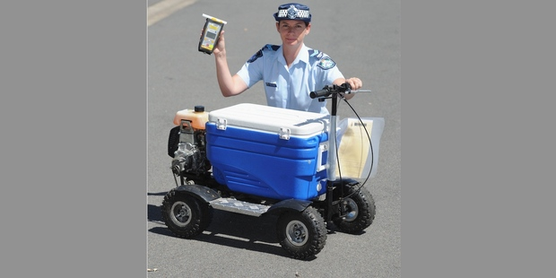 Snr Cnst Kelly Miles with a motorized esky that a man was alleged to have ridden in public whilst drunk. Photo: Alistair Brightman / Fraser Coast Chronicle