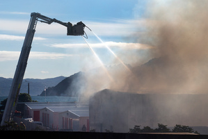 Smoke billowing from the Kiwi Storage facility as firefighters struggle to control the blaze. Photo / Mark Mitchell