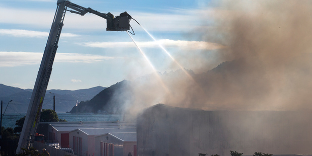 Loading Smoke billowing from the Kiwi Storage facility as firefighters struggle to control the blaze. Photo / Mark Mitchell