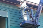 A worker removes asbestos-laden fibrolite panels from the Kaikohe Hotel's eaves.