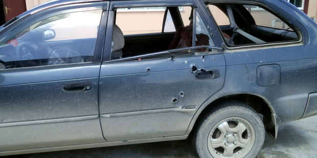Bullet holes are seen in the car in which Associated Press photographer Anja Niedringhaus and AP reporter Kathy Gannon were travelling when they were shot by an Afghan policeman. Photo / AP
