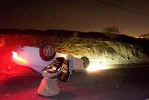 A car sits overturned on a highway in the Carbon Canyon area of Brea, California. Photo / AP