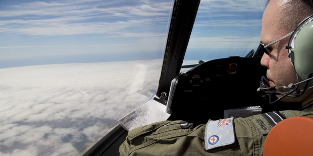 Flight Lieutenant Jayson Nichols looks out of the cockpit of a Royal Australian Air Force AP-3C Orion. Photo / AP
