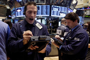 Trader Gregory Rowe, left, works on the floor of the New York Stock Exchange. File photo / AP