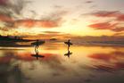 Surfers on Papamoa Beach. Photo / Jon Goldie