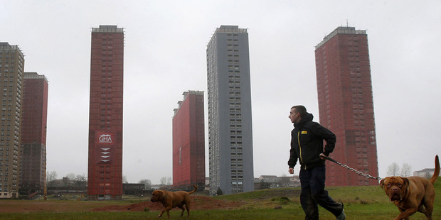 A man walks his dog near the 30-story Red Road apartment blocks which were built in the 1960s as modern replacements for slum housing in Glasgow. Photo / AP