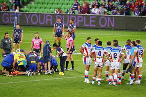 Knights players form a huddle was Alex McKinnon is attended to. Photo / Getty Images