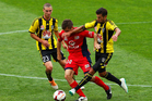 Cameron Watson of Adelaide United is tackled by Vince Lia of the Phoenix while Matthew Ridenton looks on. Photo / Getty Images