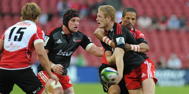 Johnny Mc nicholl and Matt Todd of Crusaders are tackled by Courtnall Skosana with Andries Coetzee looking on of Lions. Photo / Getty Images