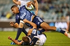 The Blues' Charles Piutau runs over Lachlan McCaffrey of the Brumbies in their clash at Canberra. Photo / Getty Images